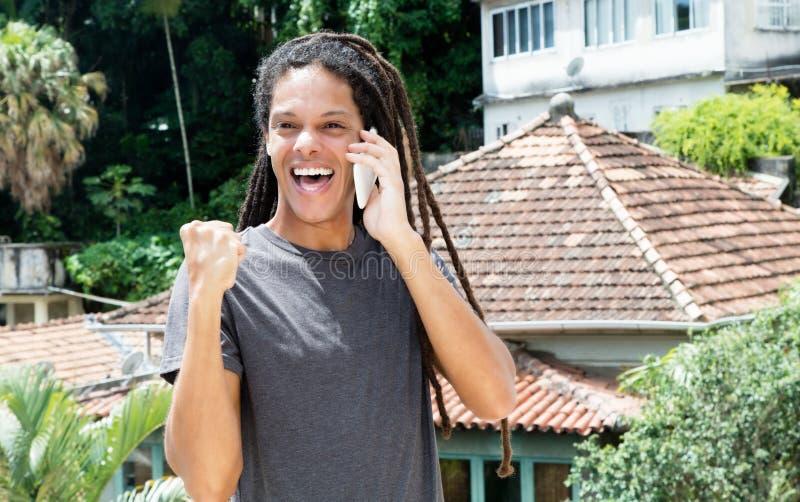 Latin - amerikansk ung vuxen man med dreadlocks som hurrar på telefonen royaltyfria bilder