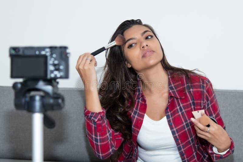 Latin - amerikansk vloggerflicka som framlägger skönhetsmedel i den videopd bloggen arkivbild