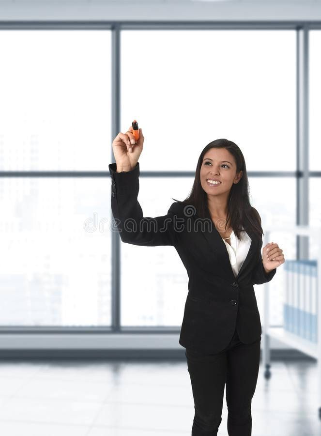 Latin business woman in formal suit writing with marker on invisible virtual screen or board at modern office stock image