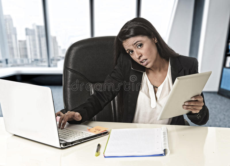 Latin business woman suffering stress working at office compute stock photography