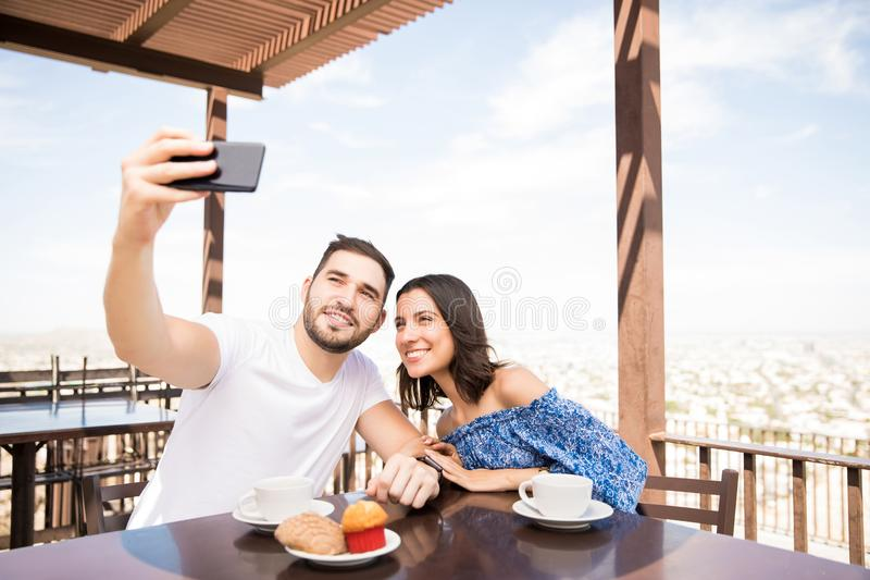 Latin couple taking selfie while sitting in cafe outdoors. Happy couple in love taking selfie portrait while having breakfast stock photos