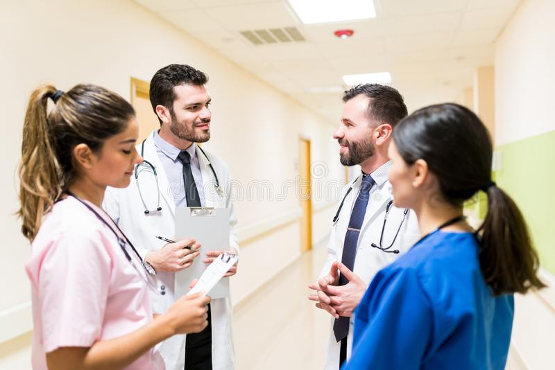 Latin Coworkers Discussing In Corridor At Hospital stock images