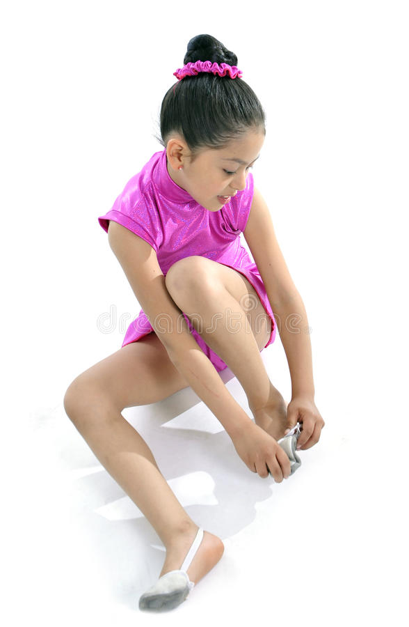 Latin cute young little girl in dancing practice putting on ballet shoe royalty free stock photos