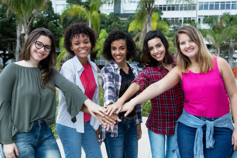 5 latin e caucasianos e as mulheres afro-americanos mantêm-se junto imagem de stock