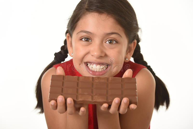 Latin female child holding with both hands big chocolate bar in front of her happy smiling face stock images
