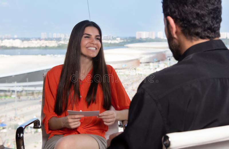 Latin female presenter asking a famous celebrity at tv studio. Beautiful latin female presenter asking a famous celebrity at tv studio royalty free stock photography