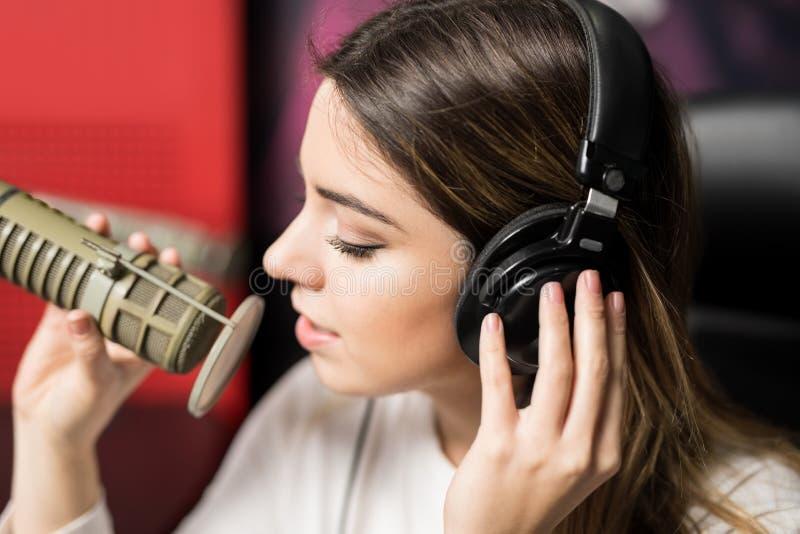 Latin female singer singing at radio station royalty free stock photo