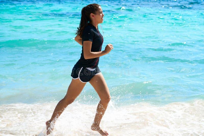Latin girl running in caribbean shore beach. Of Mayan Riviera of Mexico royalty free stock photo