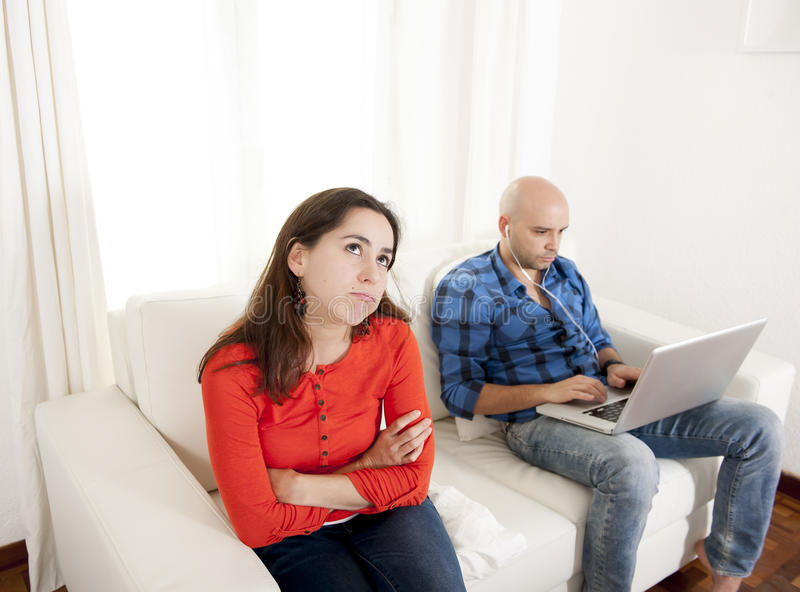 Latin girlfriend unhappy , angry and frutrated with boyfriend playing on laptop stock images