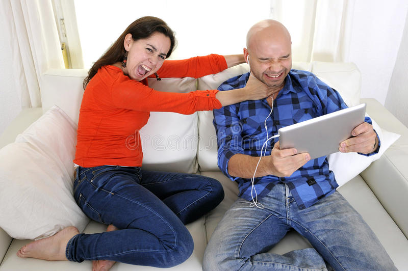 Latin girlfriend unhappy , angry and frutrated with boyfriend playing on laptop royalty free stock photo