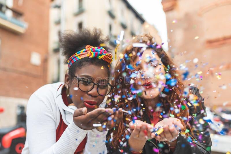 Latin Girls Blowing Confetti Outdoors stock image