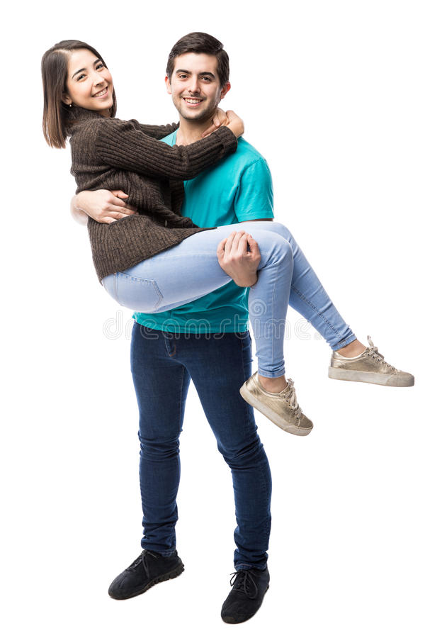 Latin guy lifting his girlfriend royalty free stock photo