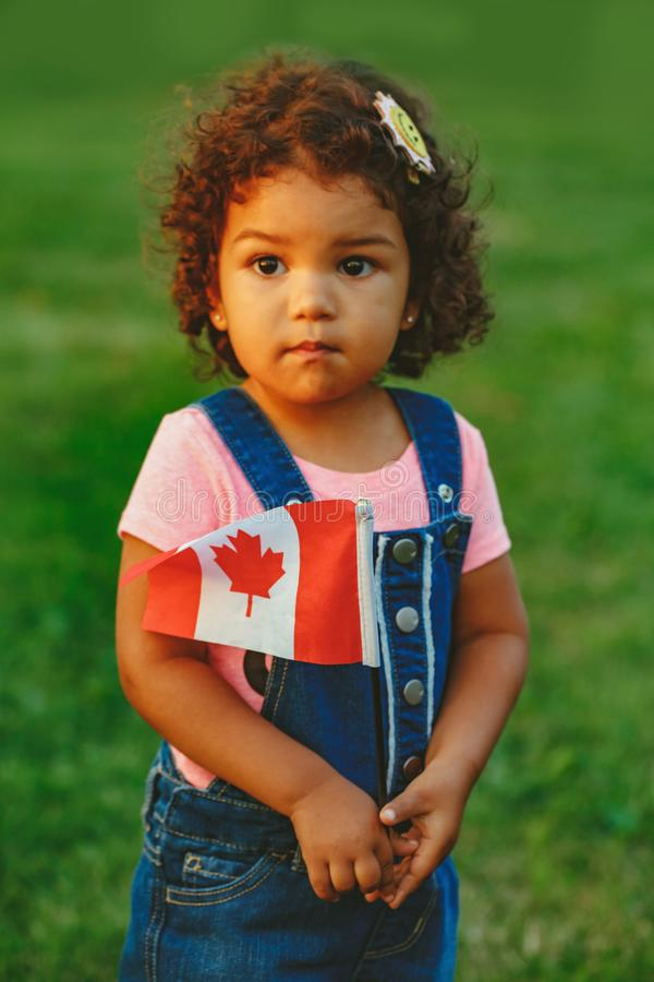 Latin hispanic baby toddler girl holding waving Canadian flag. Portrait of adorable cute little latin hispanic baby toddler girl holding waving Canadian flag stock photography
