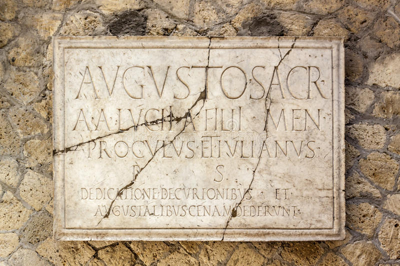 Latin inscription on Herculaneum marble. A marble plaque inscribed with Latin text hangs on a wall in Herculaneum at the foot of Mount Vesuvius on the Bay of royalty free stock photo