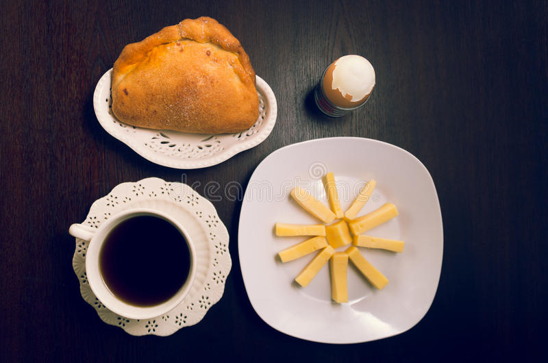 Latin inspired breakfast on dark wood table including slices of cheese placed upon white square plate next to orange royalty free stock photos