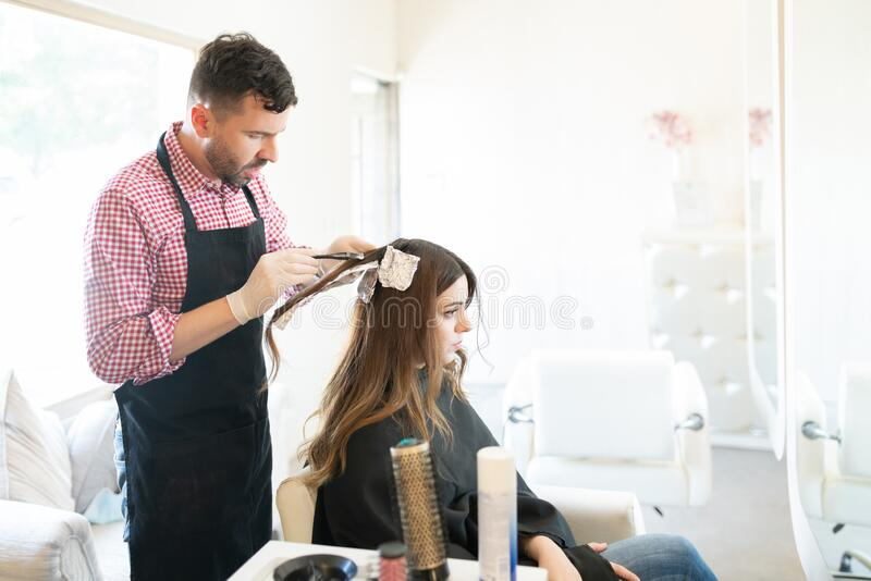 Hispanic Hairstylist Dyeing Hair Of Female Client. Latin male hairdresser applying dye on hair of young women at salon stock photo
