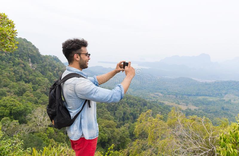 Latin Man With Backpack Take Photo Of Landscape From Mountain Top On Cell Smart Phone royalty free stock images