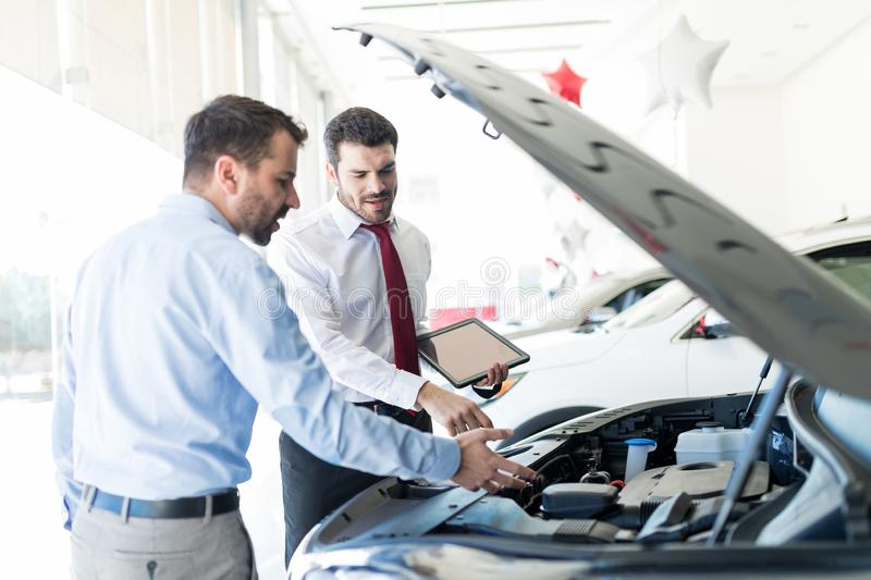 Dealer And Customer Discussing Over Car Engine royalty free stock photography