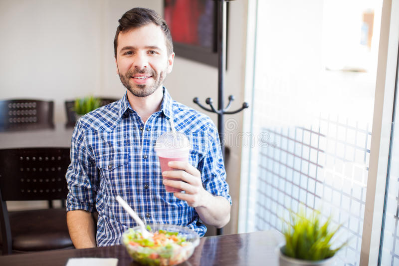 Latin man eating some healthy food. Portrait of a young Latin man eating some healthy food and enjoying a smoothie alone at a restaurant stock image