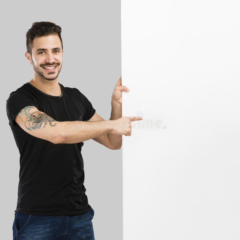 Latin man holding a blank billboard. Beautiful latin man smiling and pointing to a blank billboard royalty free stock photo