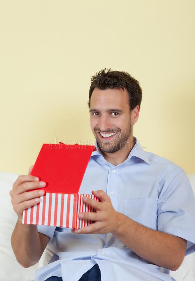 Latin man opening a gift in his living room. Attractive latin man opening a gift box in his living room and looking at camera royalty free stock photos
