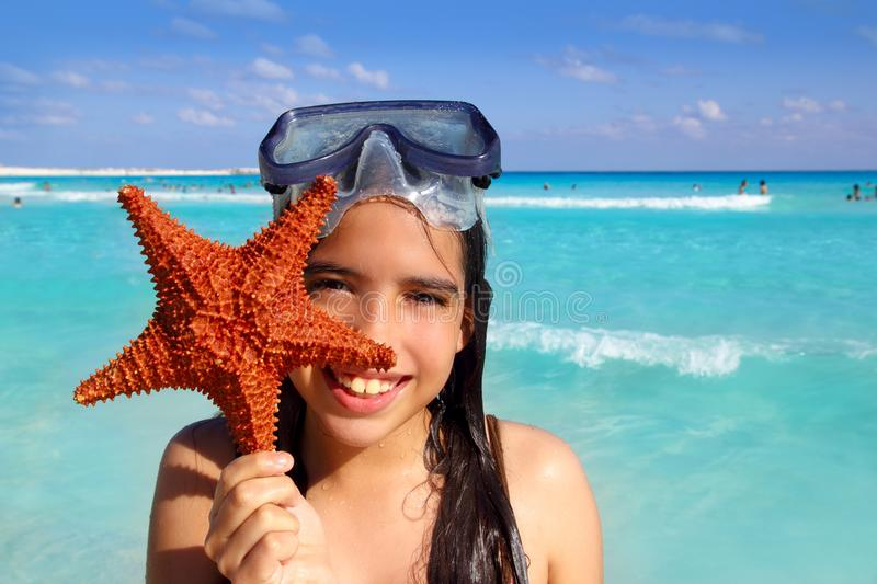 Latin tourist girl holding starfish tropical beach stock photography
