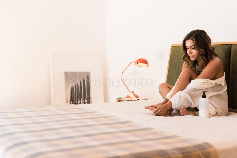Latin woman applying body cream from a container with copy space for branding royalty free stock images