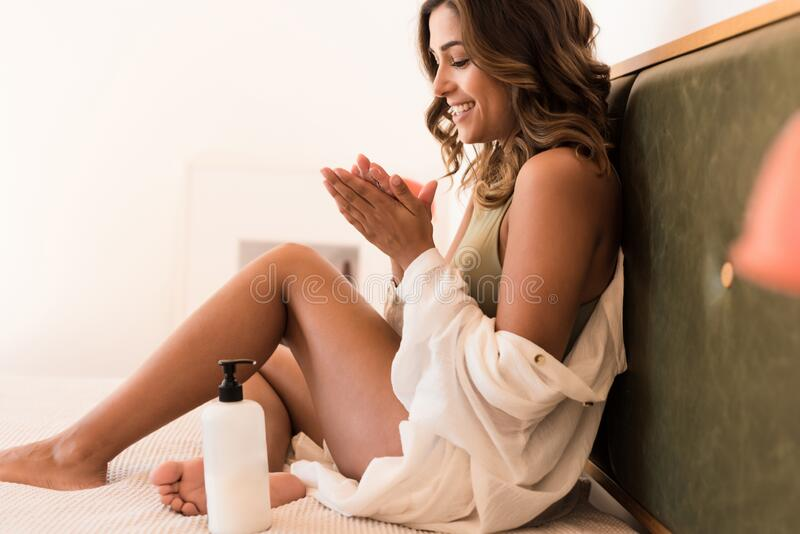 Latin woman applying body cream from a container with copy space for branding royalty free stock image