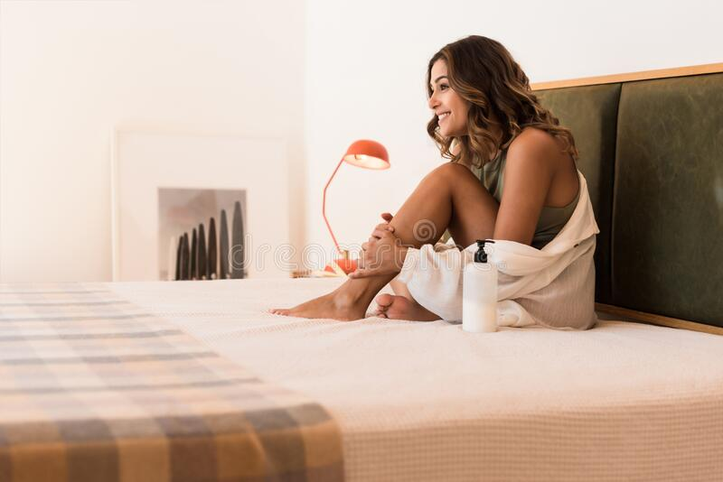 Latin woman applying body cream from a container with copy space for branding stock photos