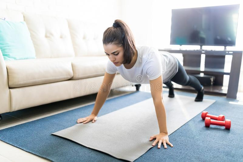 Latin woman doing push ups at home. Fit young latin woman doing push ups on exercise mat at home royalty free stock photo