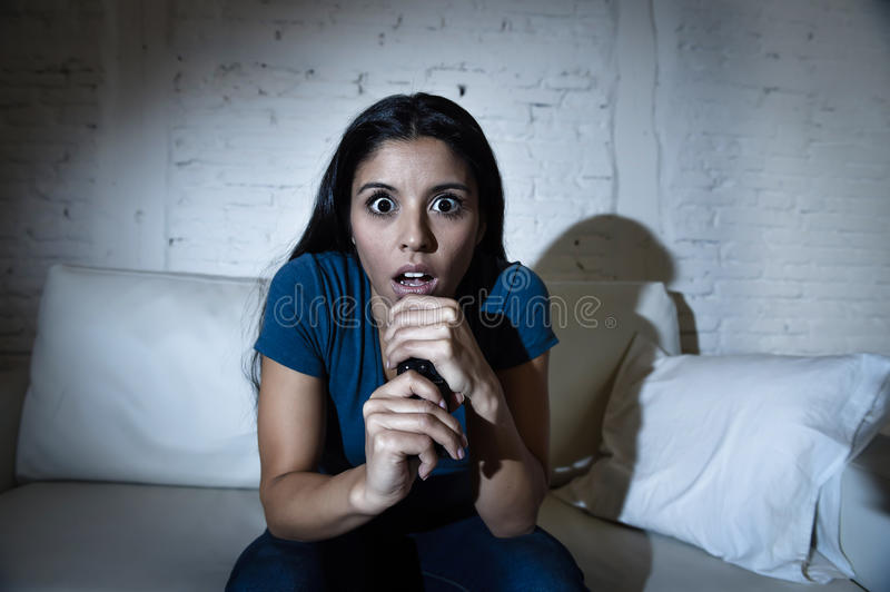 Latin woman at home sofa couch in living room watching television scary horror movie or suspense thriller royalty free stock photos