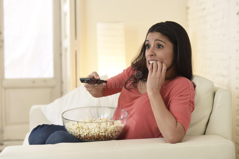 Latin woman sitting at home sofa couch in living room watching television scary horror movie. Young beautiful latin woman sitting at home sofa couch in living royalty free stock images
