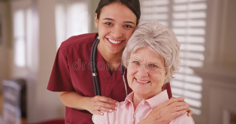 Latina caretaker with senior woman smiling stock photography