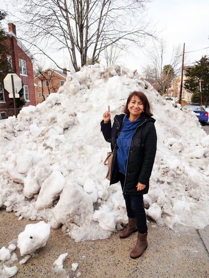 Latina delante del montón de la nieve imagenes de archivo