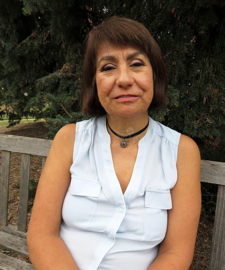 Latina en un banco de parque imágenes de archivo libres de regalías