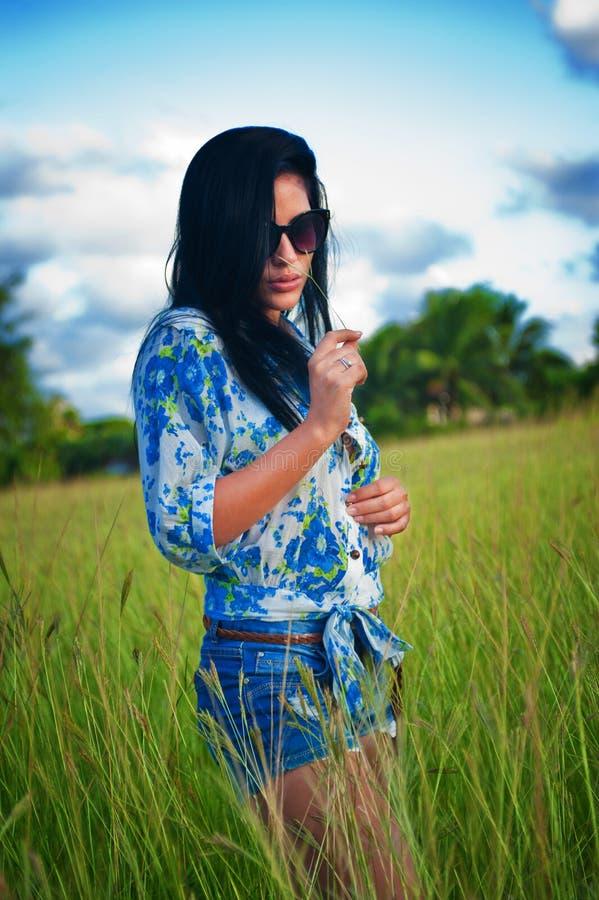 Latina-Frau mit Sonnenbrille und kurzen Hosen gehend durch das Feld stockbild