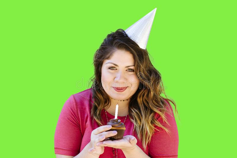 Latina Girl Holds a Birthday Cupcake while Smiling on Green Screen stock photography