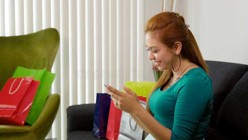 Latina Girl With Shopping Bags Typing On Mobile Phone stock photos