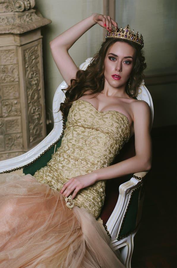 Latina hermosa con los pechos magníficos en un vestido blanco que miente en el sofá hermoso imágenes de archivo libres de regalías