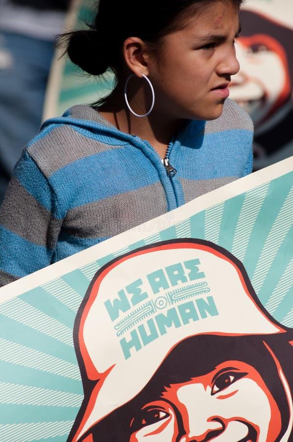Latina-Mädchen mit Plakat: Wir sind menschlich stockbild