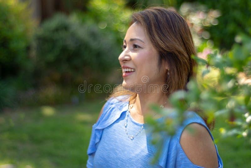 Latina-Mutter, die im Hinterhof vor rotem leaved Busch l?chelt lizenzfreie stockbilder
