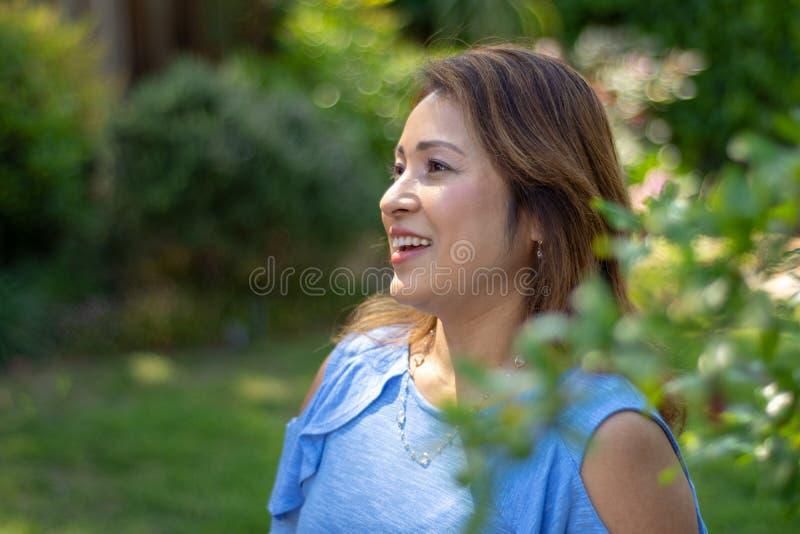 Latina-Mutter, die im Hinterhof vor rotem leaved Busch l?chelt stockbilder
