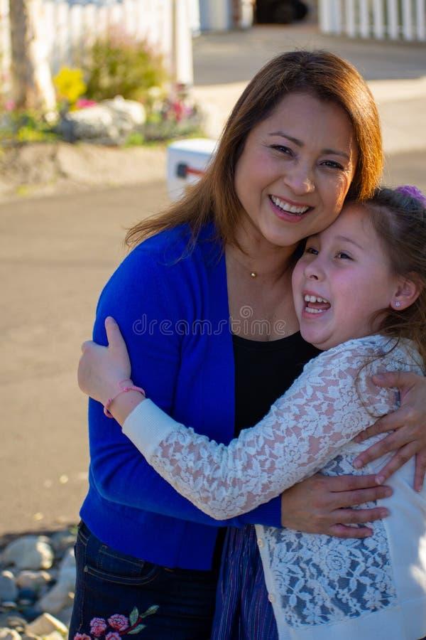 Latina-Mutter und -tochter, die draußen unter einem Baum lächeln und lachen lizenzfreie stockfotos