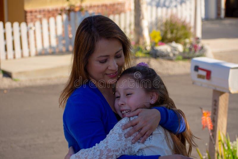 Latina-Mutter und -tochter, die draußen unter einem Baum lächeln und lachen stockfotografie