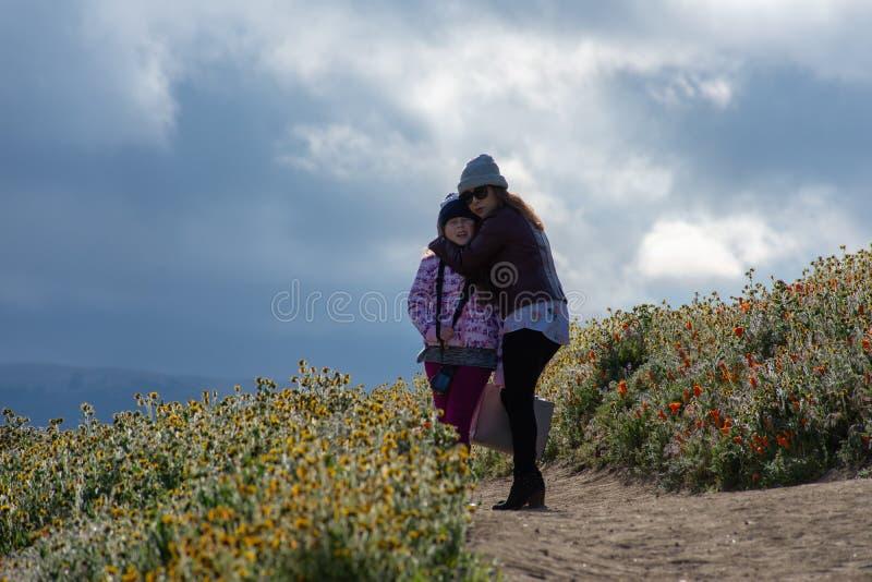 Latina-Mutter und Tochter vor Wüste Kalifornien-Mohnblumenfeld auf Weg mit den orange und gelben Blumen stockfoto