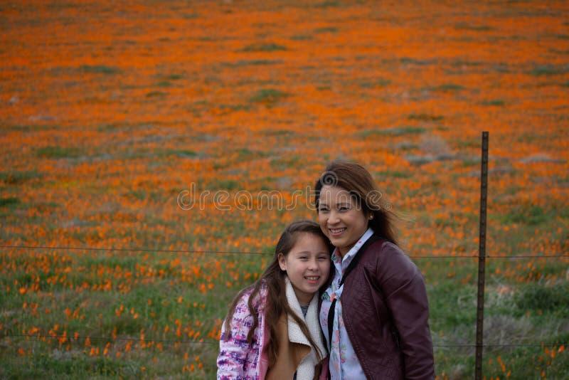 Latina-Mutter und Tochter vor Wüste Kalifornien-Mohnblumenfeld orange bokeh lizenzfreies stockfoto