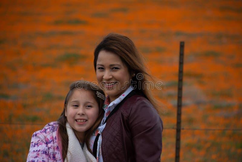 Latina-Mutter und Tochter vor Wüste Kalifornien-Mohnblumenfeld orange bokeh lizenzfreie stockfotografie