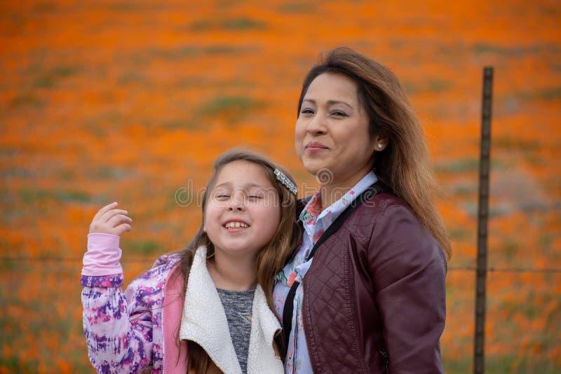 Latina-Mutter und Tochter vor Wüste Kalifornien-Mohnblumenfeld orange bokeh stockfotografie