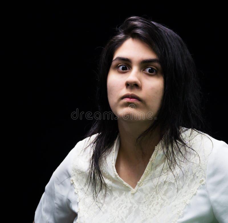 Latina som är tonårig i vit på den svarta bakgrunden royaltyfria foton