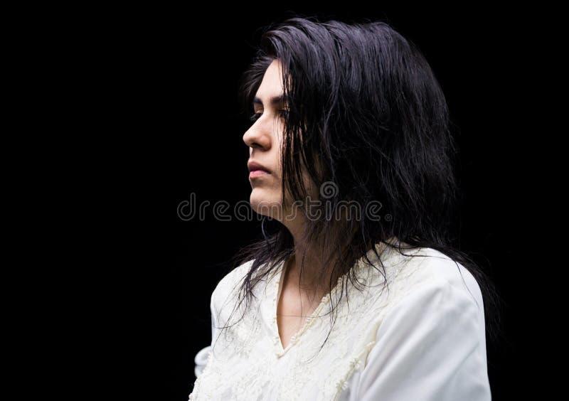 Latina som är tonårig i vit på svart bakgrund royaltyfri foto